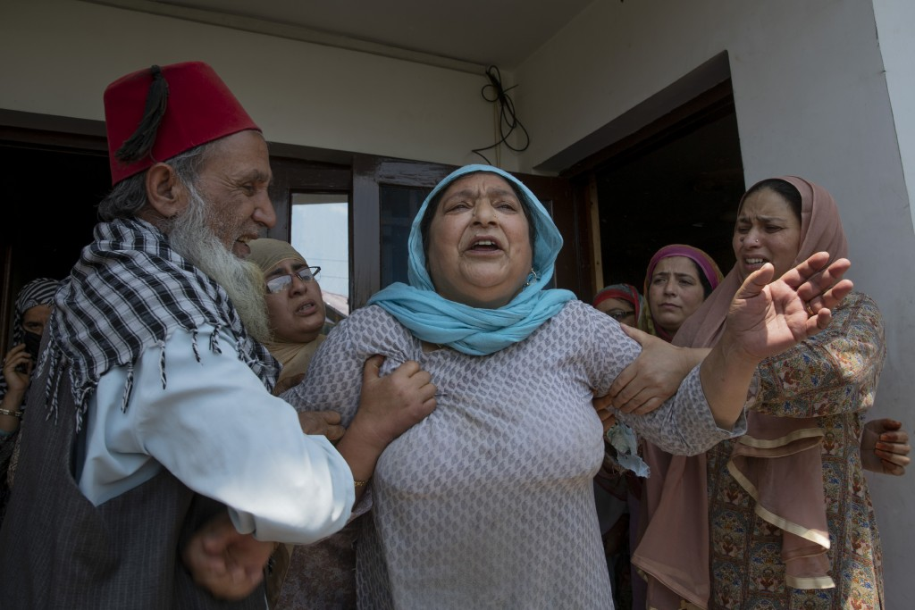 Relatives comfort the wife of civilian Bashir Ahmed Khan at their residence on the outskirts of Srinagar, Indian controlled Kashmir, Wednesday, July 1...