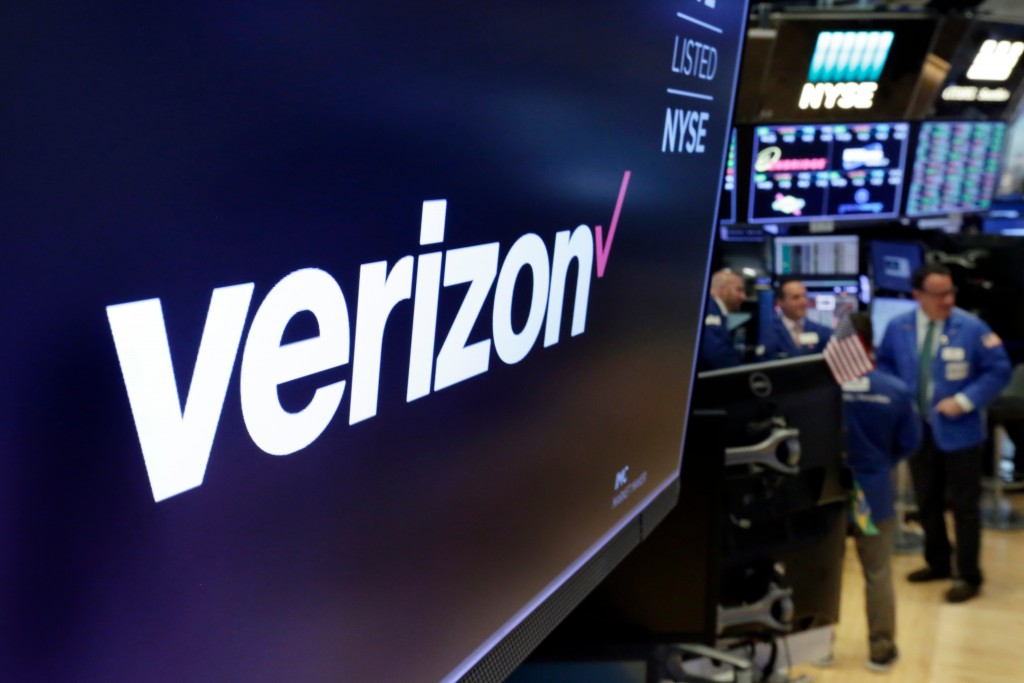 FILE - This April 23, 2018, file photo shows the logo for Verizon above a trading post on the floor of the New York Stock Exchange. Verizon's decision...
