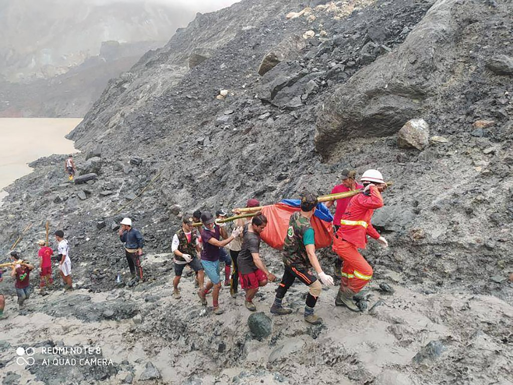 In this photo released from Myanmar Fire Service Department, rescuers carry a recovered body of a victim of a landslide from a jade mining area in Hpa...