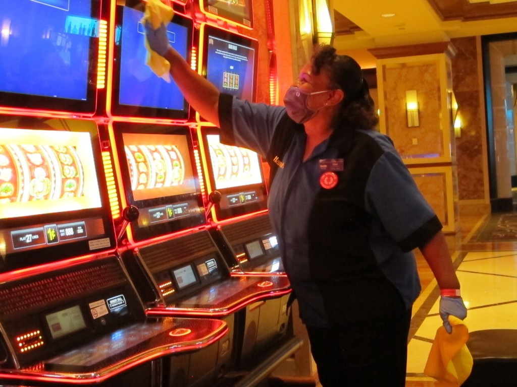 Jeorganna Barnes, a worker at Harrah's casino in Atlantic City, N.J., wipes slot machines with disinfectant Wednesday, July 1, 2020, as the casino pre...