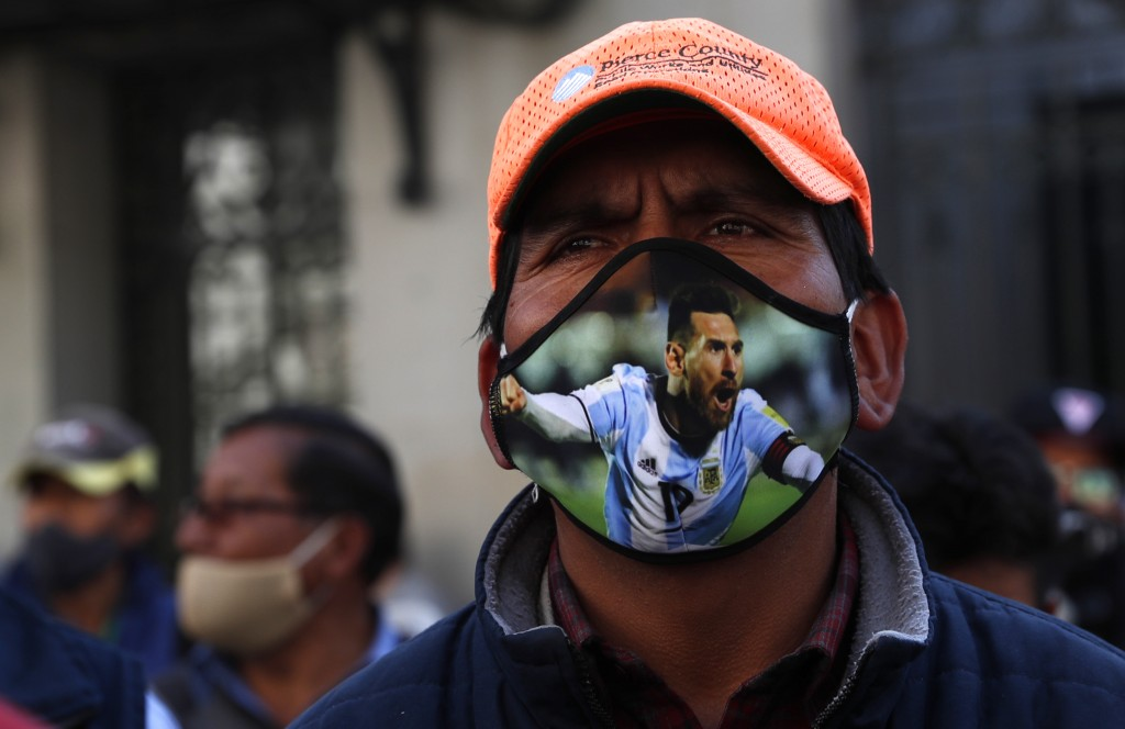 A public transport driver, wearing a protective face mask emblazoned with an image of Lionel Messi, attends a protest demanding an increase in fares b...