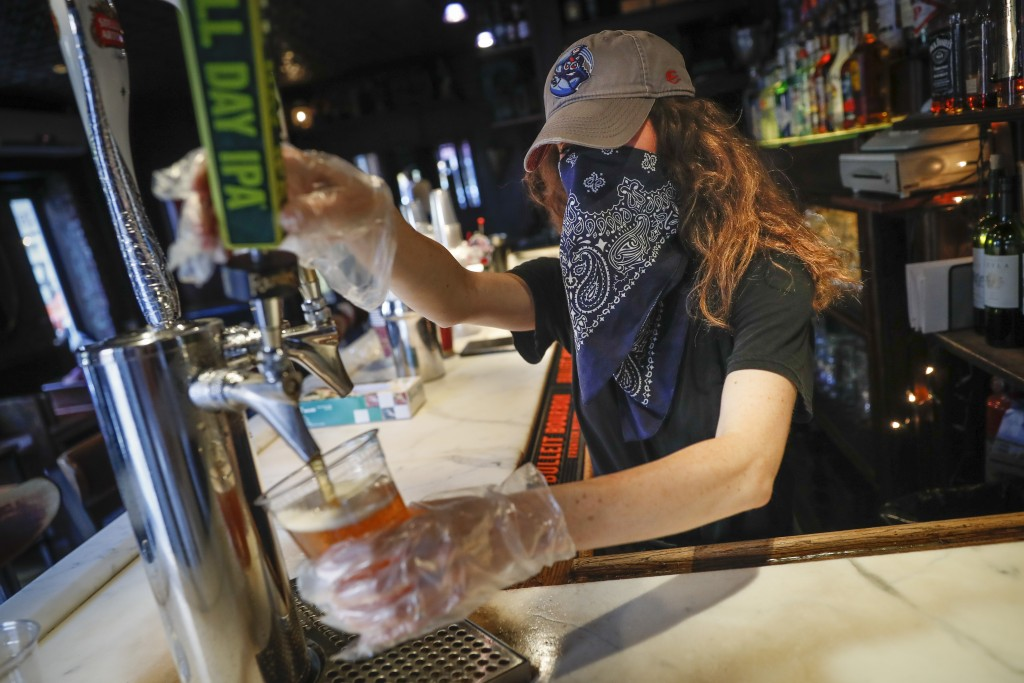 FILE - In this June 22, 2020, file photo, a bartender pours a beer for a customer at Shade Bar NYC in New York. Authorities are closing honky tonks, b...