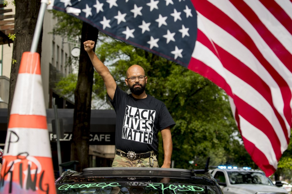 FILE - In this June 19, 2020, file photo, George Floyd's name is written on the windshield as John Coy wears a shirt that reads Black Lives Matter and...