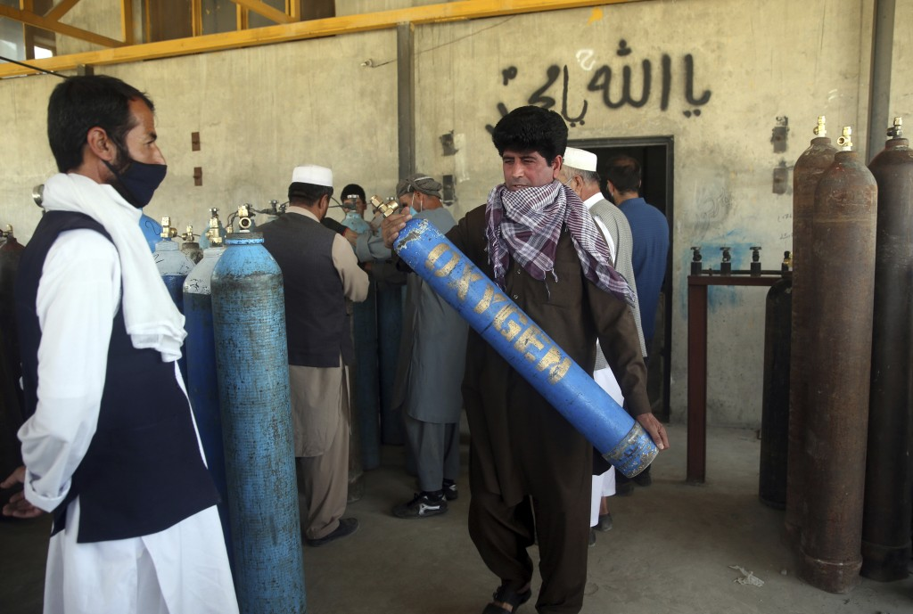 A man carries an oxygen tank from a privately owned oxygen factory, in Kabul, Afghanistan, Thursday June 18, 2020. For seven years, Najibullah Seddiqi...