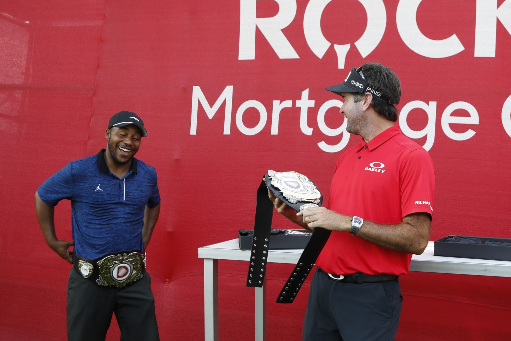 Harold Varner III, left, and Bubba Watson show off the winner's belts after their win in a nine-hole exhibition against Jason Day and Wesley Bryan ahe...