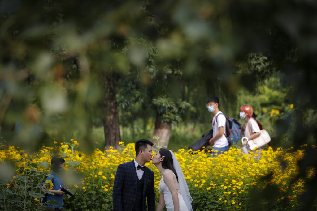 People wearing face masks to help curb the spread of the coronavirus pass by a newly weds kissing as they posing for wedding photos at the Olympic For...