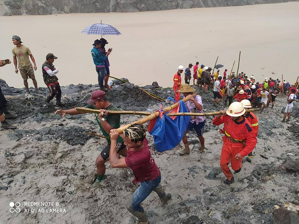 In this photo released from Myanmar Fire Service Department, rescuers carry a recovered body of a victim in a landslide from a jade mining area in Hpa...