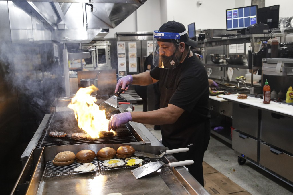 A cook prepares a meal at Slater's 50/50 Wednesday, July 1, 2020, in Santa Clarita, Calif. California Gov. Gavin Newsom has ordered a three-week closu...