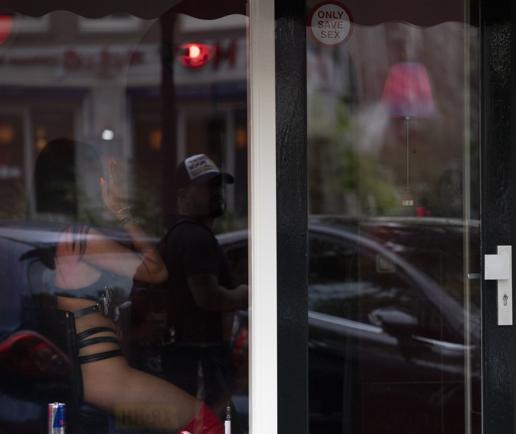 A sex worker shields her face from the photographer as a passing man is reflected in the window after a further ease of corona virus restrictions in A...