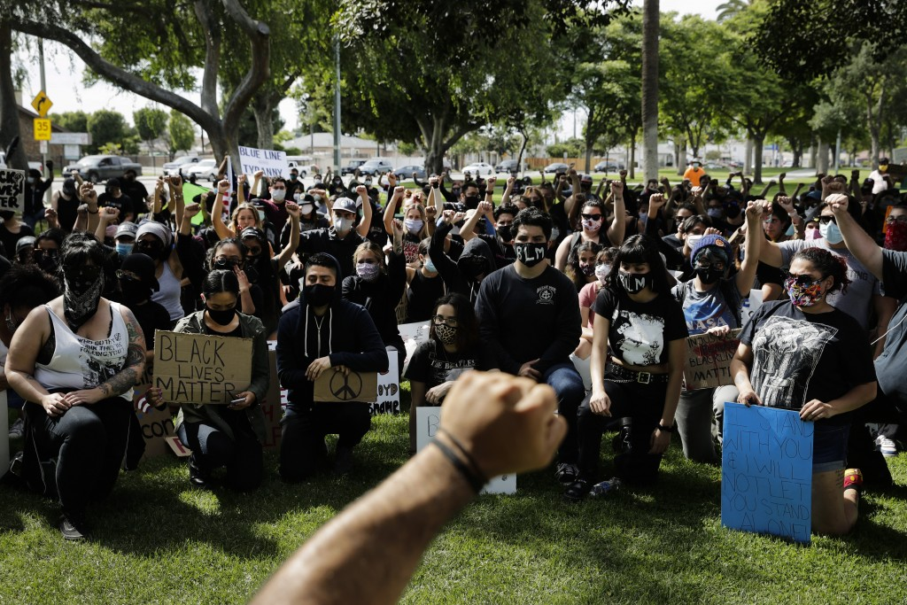 FILE - In this June 1, 2020, file photo, demonstrators raise their fists during a protest over the death of George Floyd in Anaheim, Calif. Thousands ...