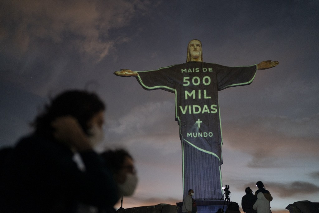 "The Christ the Redeemer statue is lit up with a message that reads in Portuguese; ""More than 500 thousand lives world"" in reference to the people who ..."