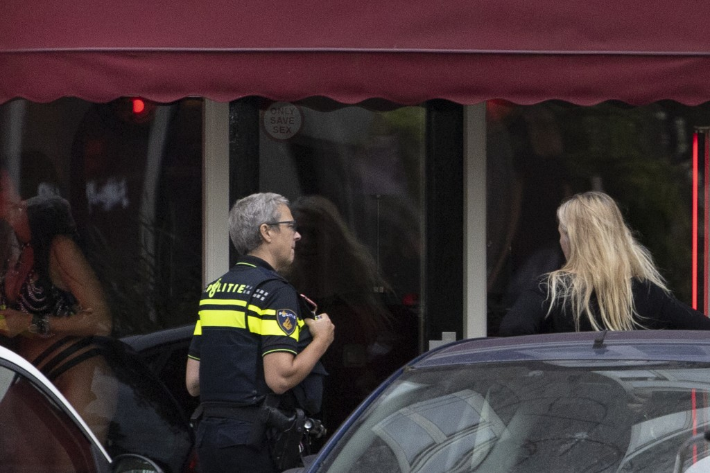 A police officer talks to a woman, right, as a sex worker, left, applies make up after a further ease of corona virus restrictions in Amsterdam, Nethe...