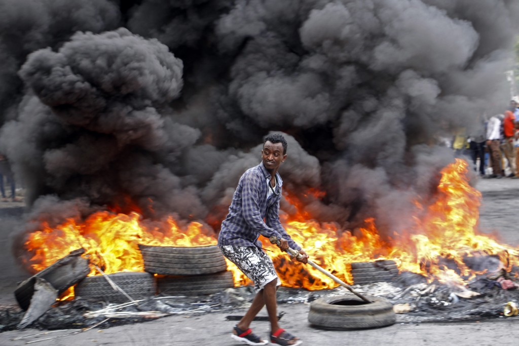 FILE - In this Saturday, April 25, 2020 file photo, a Somali man protests against the killing of at least one civilian during the overnight curfew, wh...