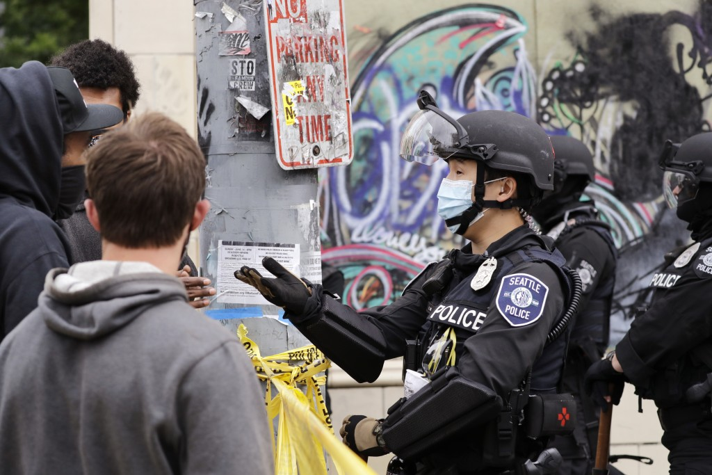 A police officer engages with a protester Wednesday, July 1, 2020, in Seattle, where streets had been blocked off in an area demonstrators had occupie...
