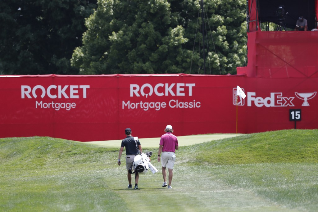 Aaron Baddeley, right, and his caddie walk up to the 15th green during a practice round for the Rocket Mortgage Classic golf tournament, Wednesday, Ju...