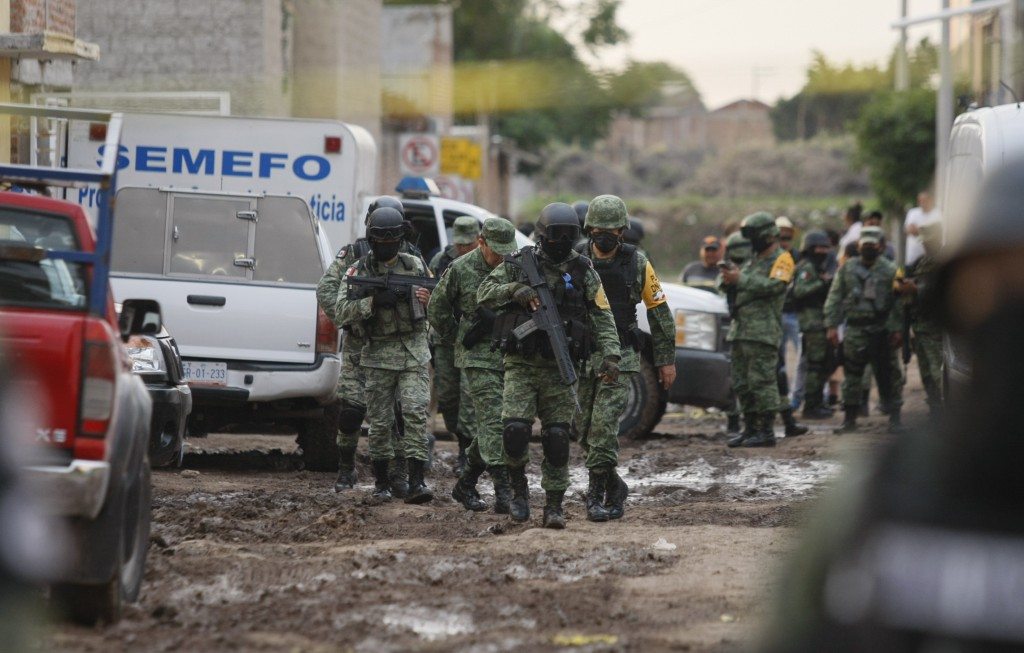 Members of the national guard walk near an unregistered drug rehabilitation center in Irapuato, Mexico, Wednesday, July 1, 2020, after gunmen burst in...