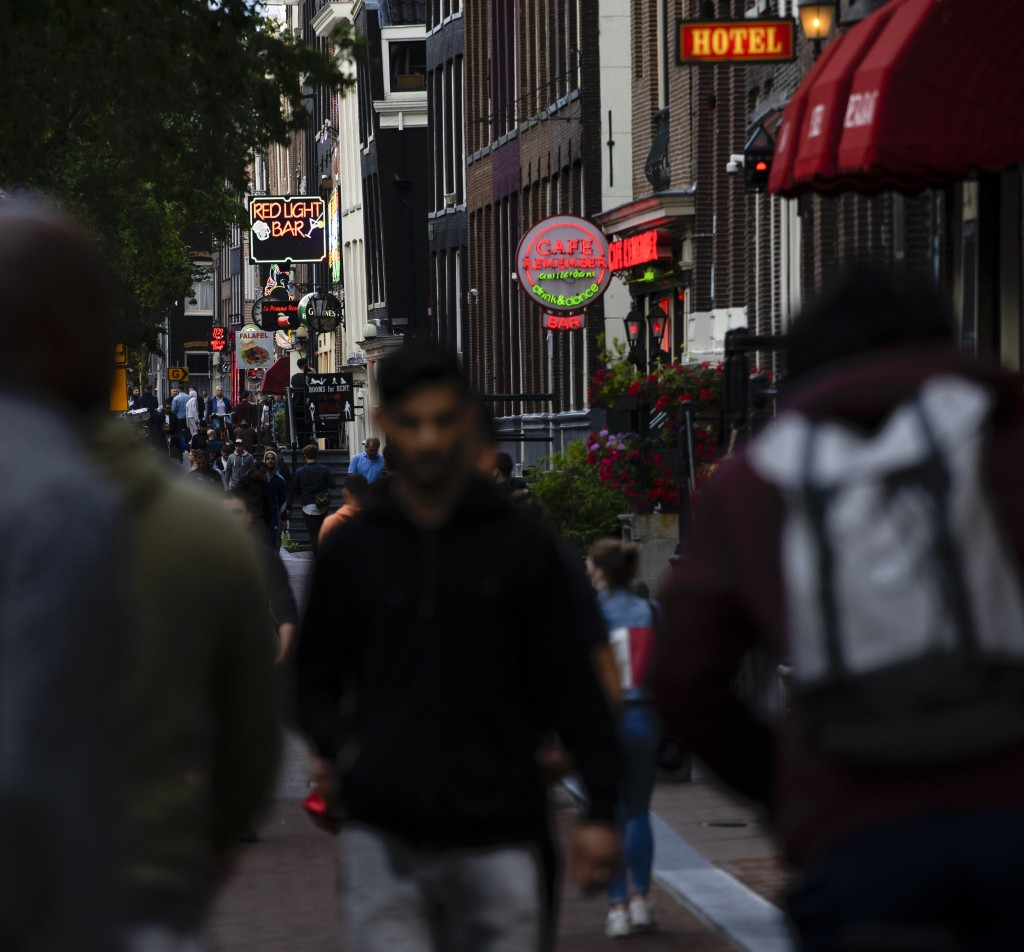 People walk in the Red Light District as sex workers welcomed clients again in Amsterdam, Netherlands, Wednesday, July 1, 2020. It wasn't quite busine...