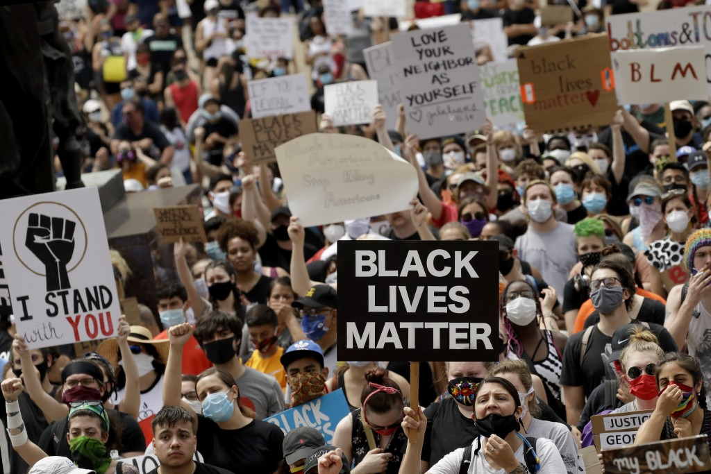 FILE - In this June 5, 2020, file photo, people hold signs as they listen to a speaker in front of city hall in downtown Kansas City, Mo., during a ra...