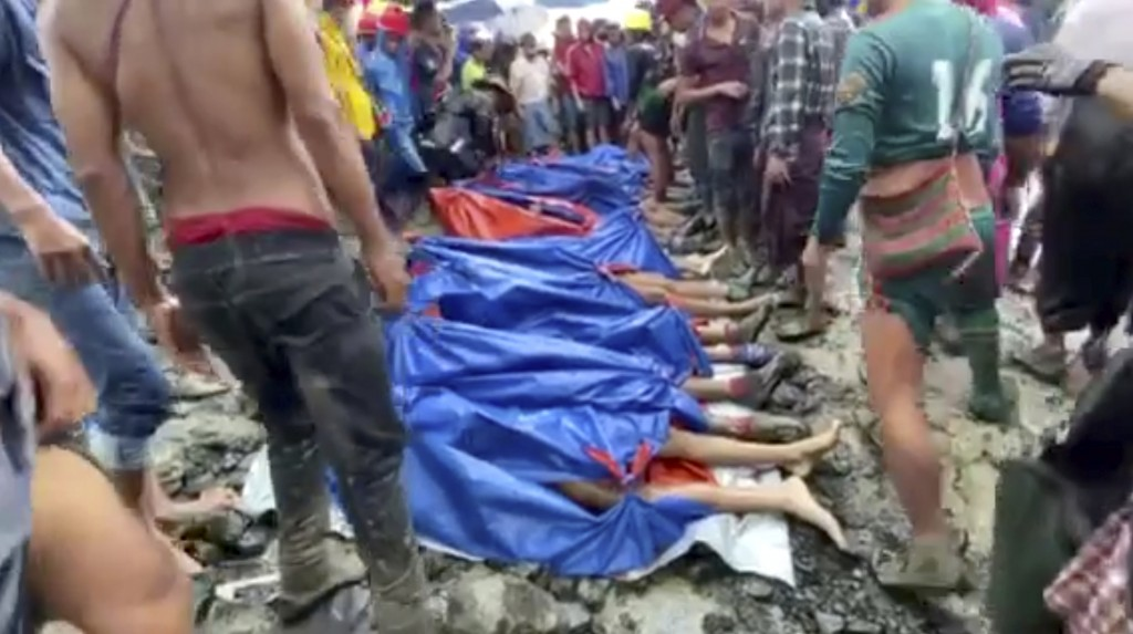 In this image made from video, people gather near the bodies of victims of a landslide near a jade mining area in Hpakant, Kachin state, northern Myan...