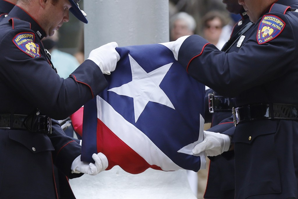 A Mississippi Highway Safety Patrol honor guard carefully folds the retired Mississippi state flag after it was raised over the Capitol grounds one fi...