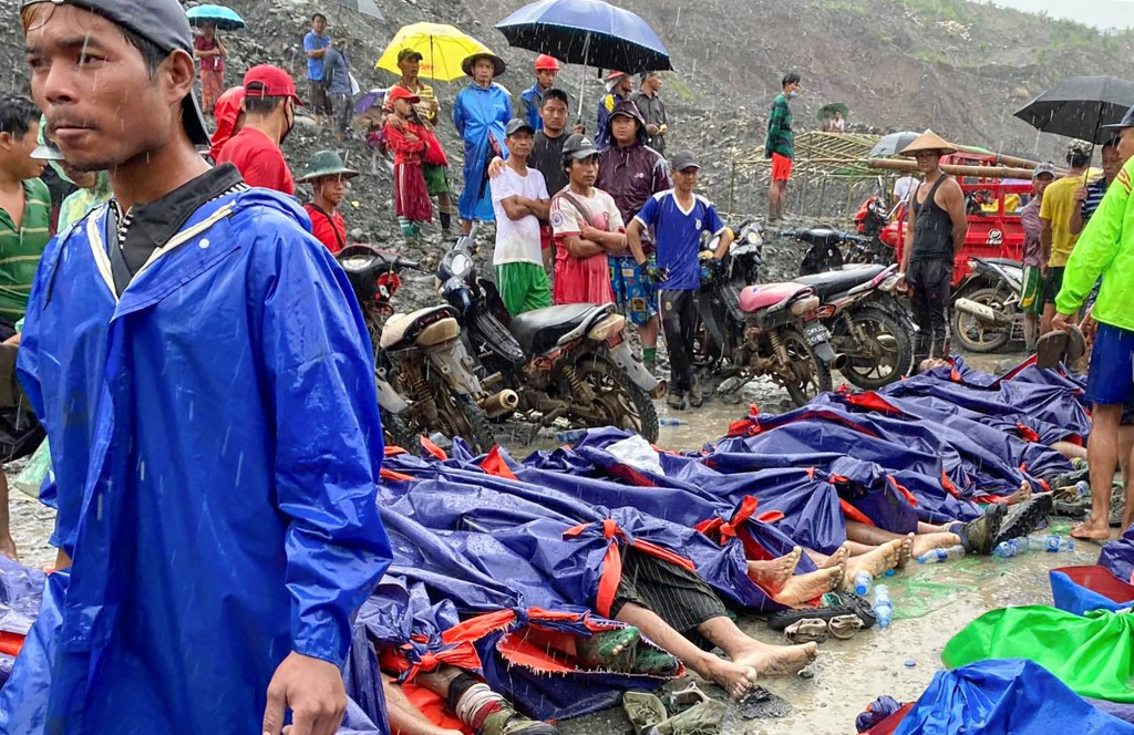 People gather near the bodies of victims of a landslide near a jade mining area in Hpakant, Kachin state, northern Myanmar Thursday, July 2, 2020. Mya...