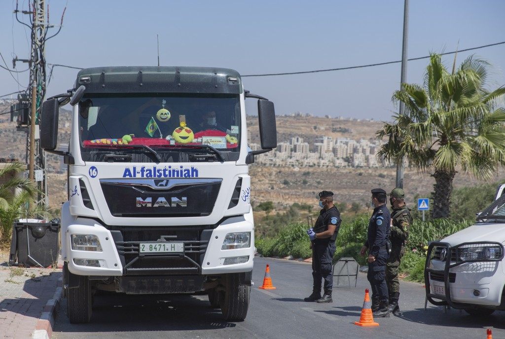A Palestinian security unit mans a checkpoint at an entrance of in the West Bank city of Ramallah, Thursday, July 2, 2020. The Palestinian Authority h...