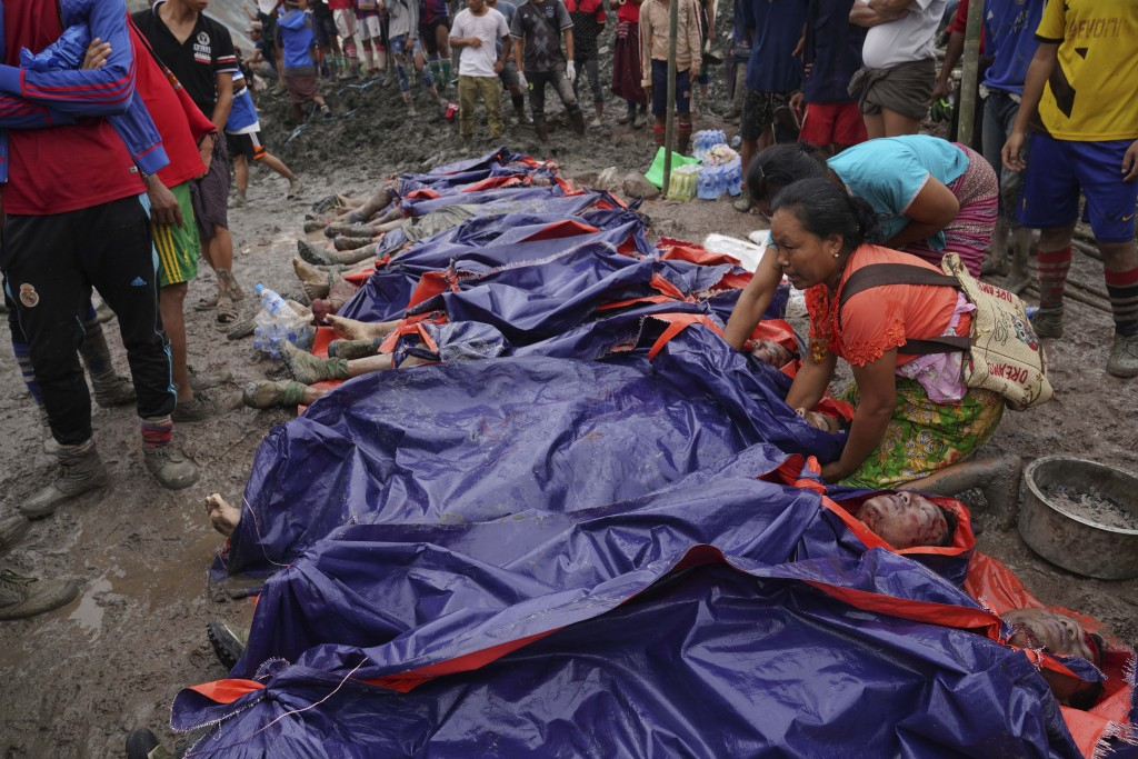 Women look at bodies shrouded in blue and red plastic sheets placed in a row on the ground Thursday, July 2, 2020 in Hpakant, Kachin State, Myanmar. A...