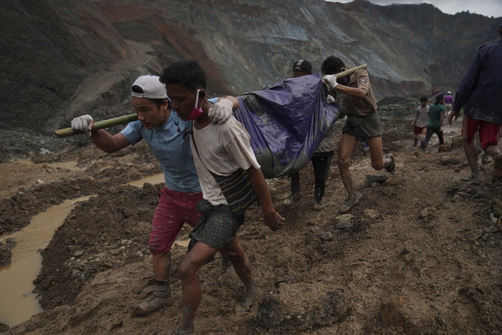 Rescue workers use poles to carry a body shrouded in blue and red plastic sheet Thursday, July 2, 2020, in Hpakant, Kachin State, Myanmar. At least 16...