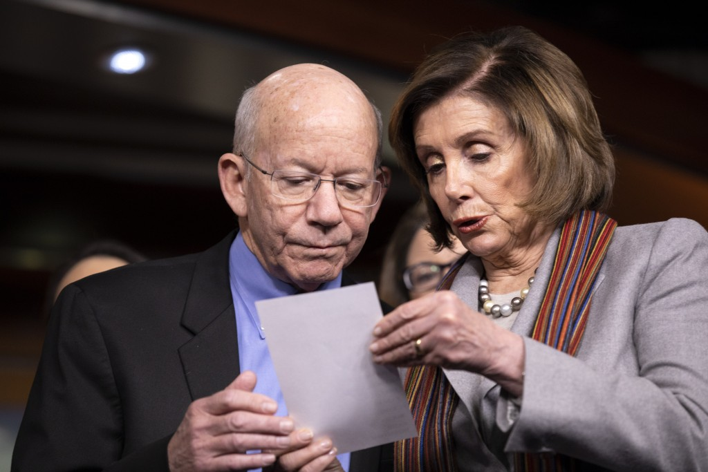 FILE - In this Jan. 29, 2020, file photo, House Speaker Nancy Pelosi of Calif., right, shows a note to Rep. Peter DeFazio, D-Ore., during a news confe...