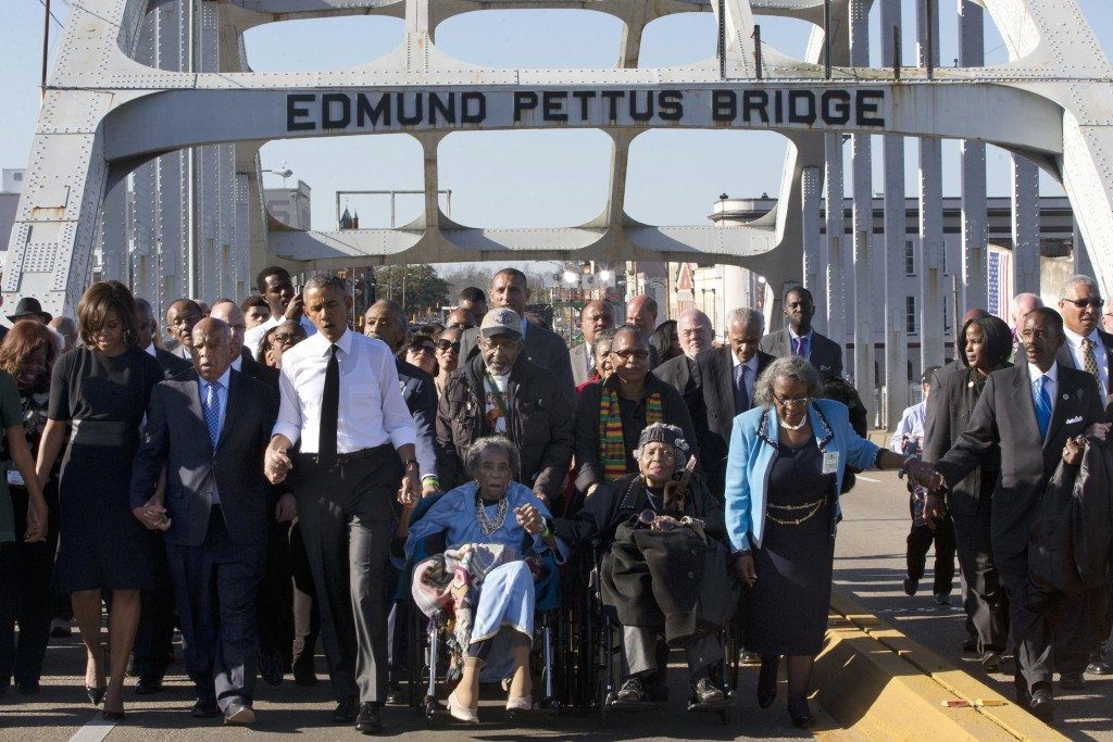 "FILE - In this March 7, 2015, file photo, singing ""We Shall Overcome,"" President Barack Obama, third from left, walks holding hands with Amelia Boynto..."