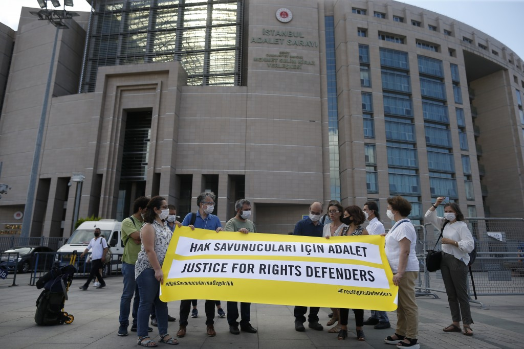 Protesters from Amnesty International stage a protest outside a court in Istanbul, Friday, July 3, 2020, where the trial of 11 prominent human rights ...