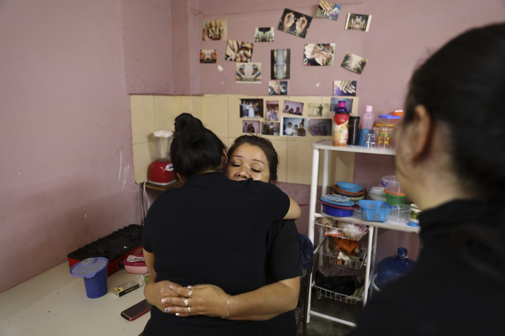 Rosa Alba Santoyo is embraced by a woman giving her condolences the day after she lost three of her adult children in an attack on the drug rehabilita...