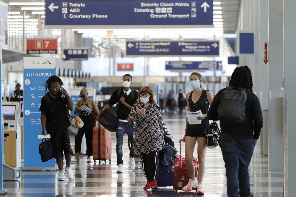 FILE - In this Tuesday, June 16, 2020, file photo, travelers walk through Terminal 3 at O'Hare International Airport in Chicago. Unions are gaining su...