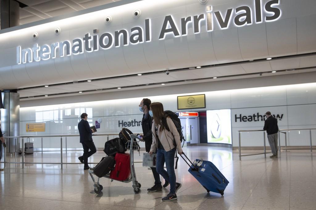 Passengers wearing face masks arrive at London's Heathrow Airport,June 8, 2020.