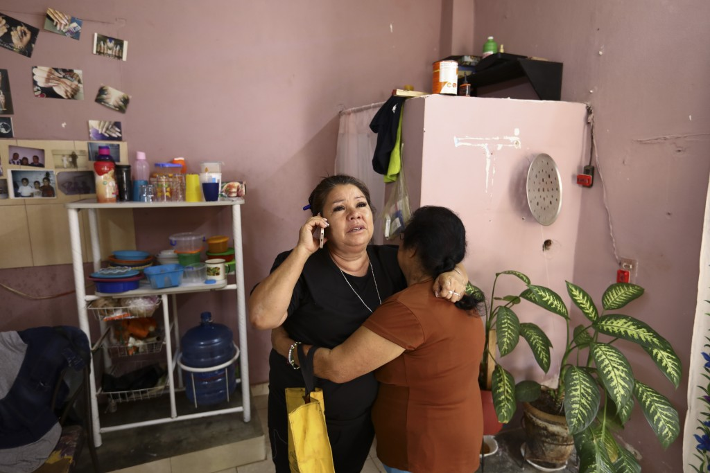 Rosa Alba Santoyo speaks on the phone and is embraced by a woman giving her condolences the day after she lost three of her adult children in an attac...