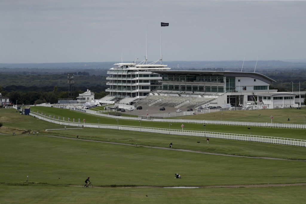People cycle, walk and sit on the Downs surrounded by the Epsom Downs Racecourse, in Epsom, England, Friday, July 3, 2020. The Derby annual horse race...