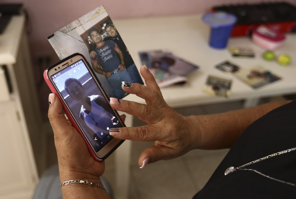 Rosa Alba Santoyo shows photos of two of her three adult children who died during an attack on a drug rehabilitation center where they were being trea...
