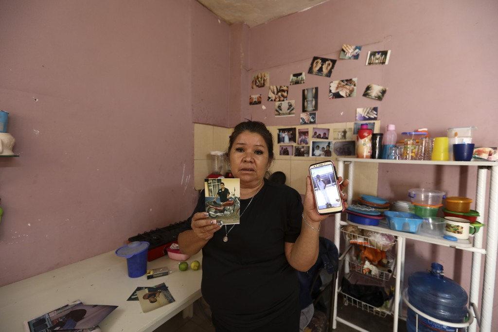 Rosa Alba Santoyo shows photos of two of her three adult children who died during an attack on the drug rehabilitation center where they were being tr...