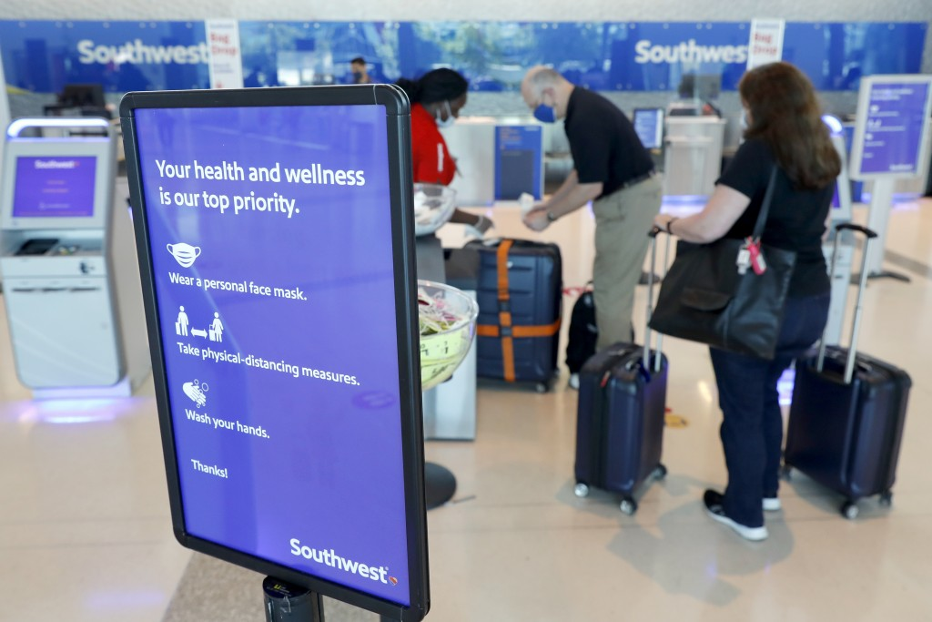 FILE - In this Wednesday, June 24, 2020, file photo, a sign reminds travelers to take safety measures against the new coronavirus as they arrive for f...