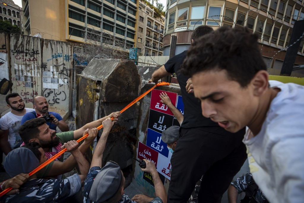 Anti-government protesters try to remove a concrete wall that was installed by security forces to prevent them from reaching the government palace in ...