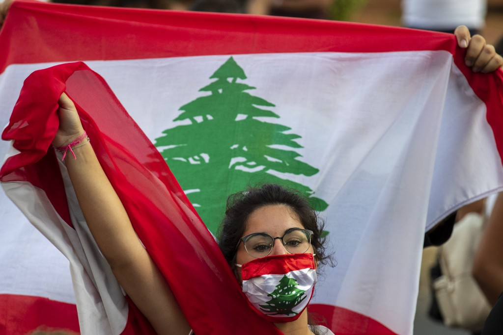 An anti-government protester shouts slogans while wearing a mask with the colors of the Lebanese flag in Beirut, Lebanon, Thursday, July 2, 2020. Majo...