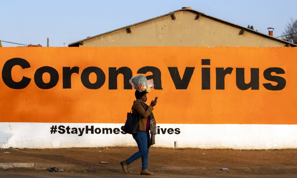 FILE - In this June 19, 2020, file photo, a woman wearing a face mask passes a coronavirus billboard carrying a message in a bid to prevent the spread...