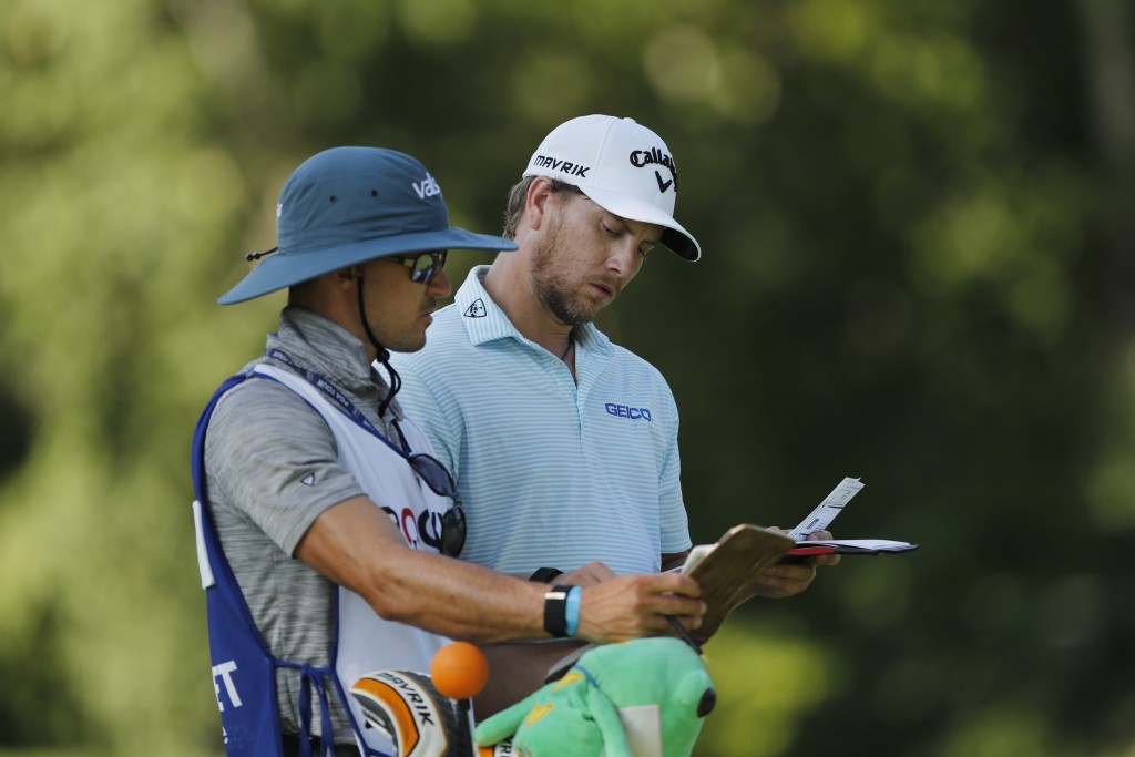 Chris Stroud checks the yardage with his caddie on the ninth tee during the first round of the Rocket Mortgage Classic golf tournament, Thursday, July...