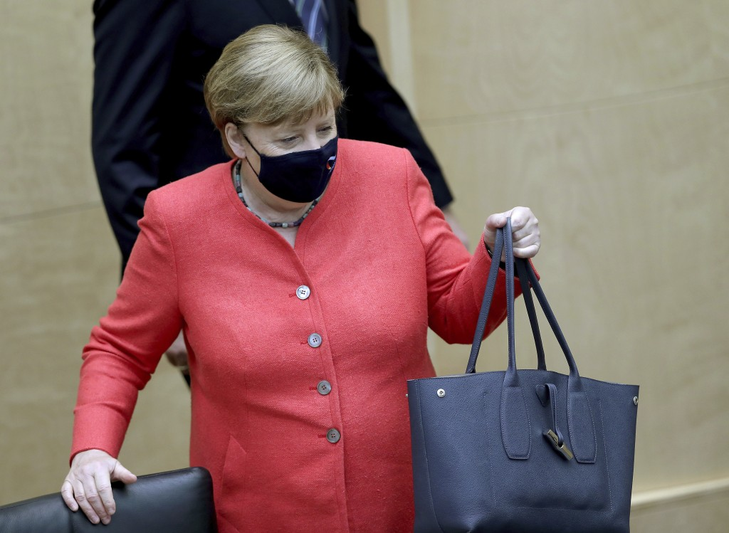 German Chancellor Angela Merkel wears a face mask as she arrives for a meeting of the upper house of the German legislative in Berlin, Germany, Friday...