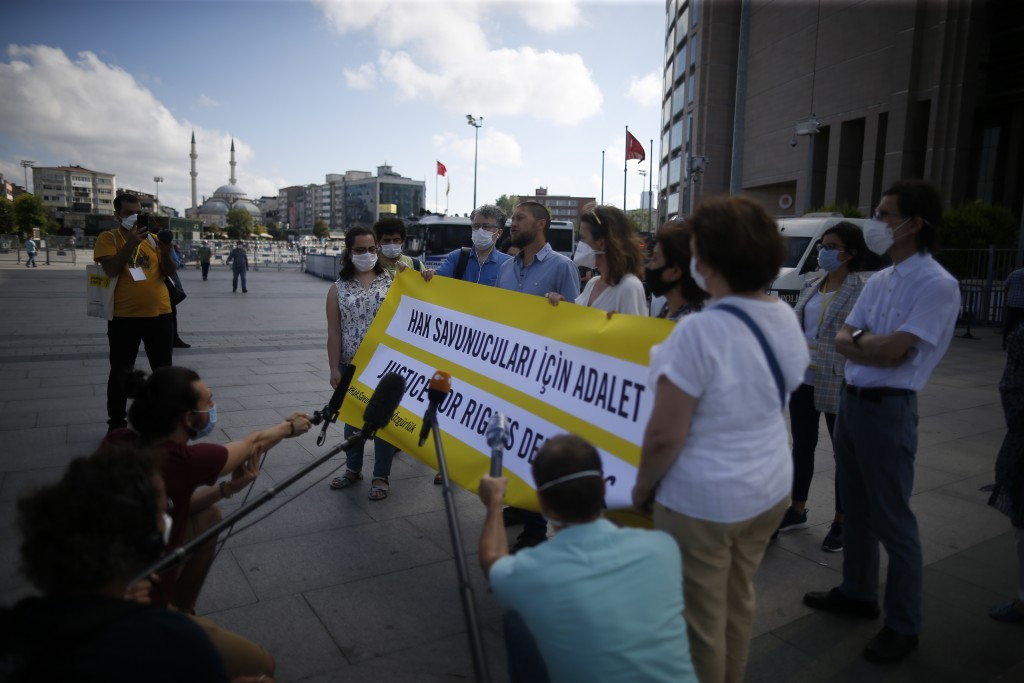 Protesters from Amnesty International talk to the media as they stage a protest outside a court in Istanbul, Friday, July 3, 2020, where the trial of ...