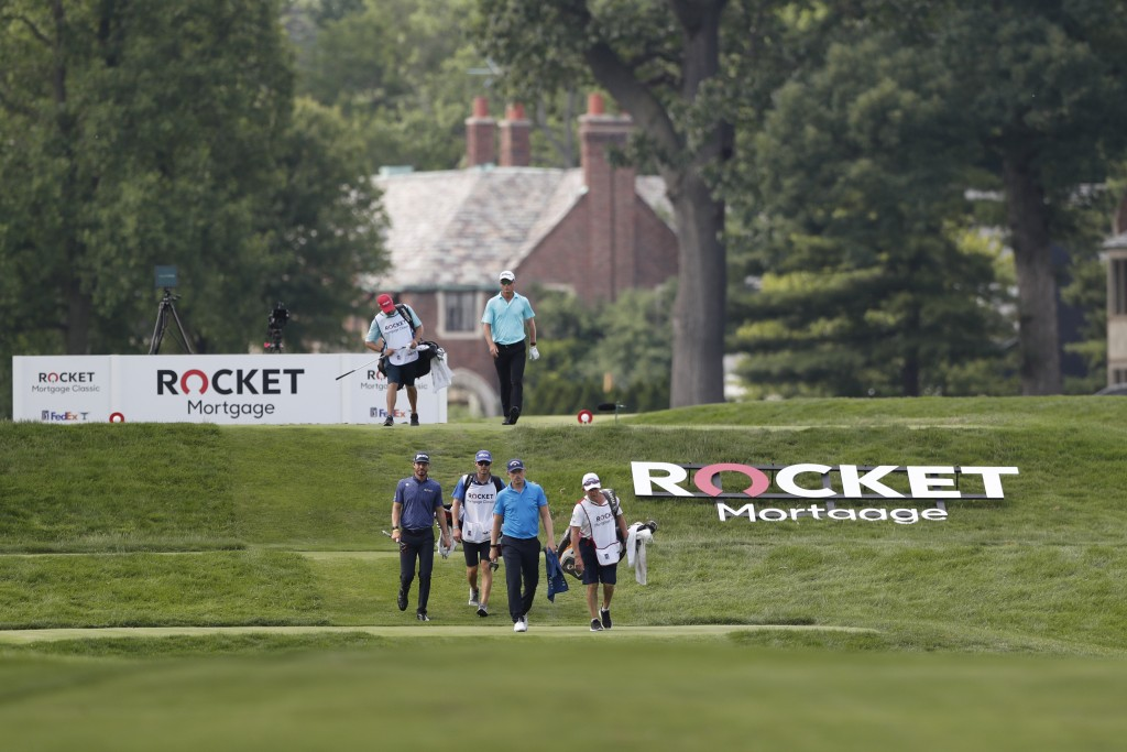 Matt Wallace, front, Sam Ryder, center, and John Senden walk on the ninth fairway during the first round of the Rocket Mortgage Classic golf tournamen...