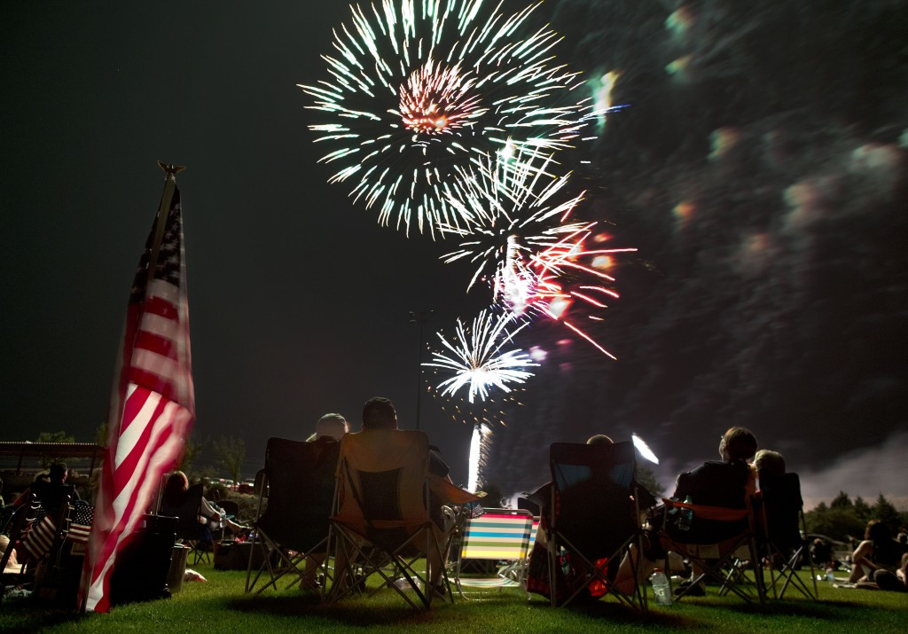FILE - In this July 4, 2013, file photo, people watch as fireworks explode overhead during the Fourth of July celebration at Pioneer Park in Prescott,...