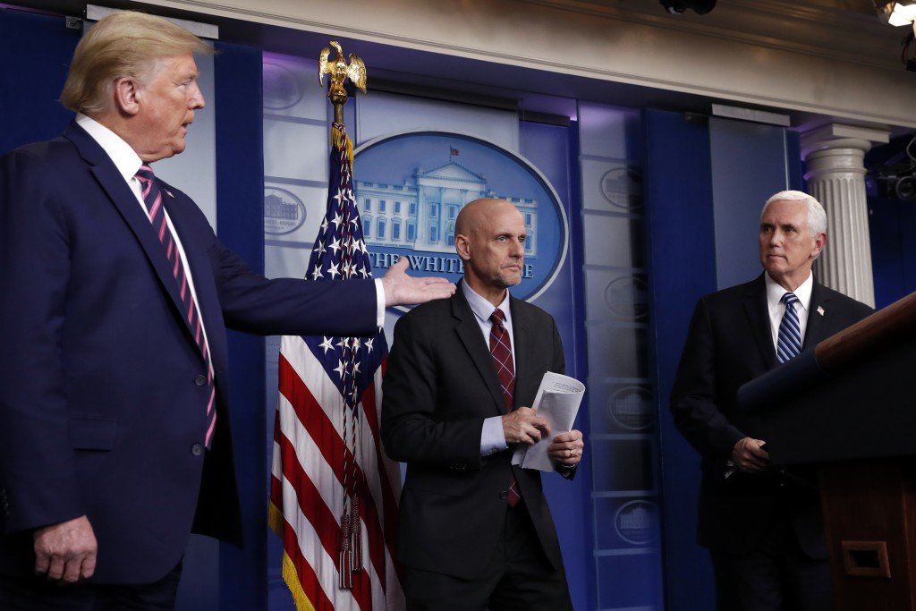 FILE - In this April 24, 2020, file photo, President Donald Trump gestures to Vice President Mike Pence as Stephen Hahn, commissioner of the U.S. Food...
