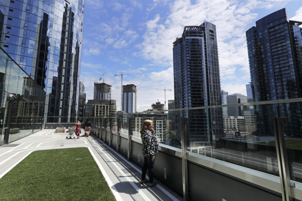 Connie Wade, center, looks out over the growing skyline of downtown Seattle, Wednesday, June 17, 2020, as she stands in an outdoor deck area at Mary's...
