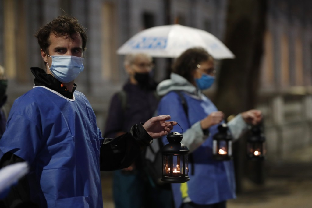 Campaigners hold lanterns outside Downing Street for British NHS medical and care workers who have died due to COVID-19, in London, Friday, July 3, 20...